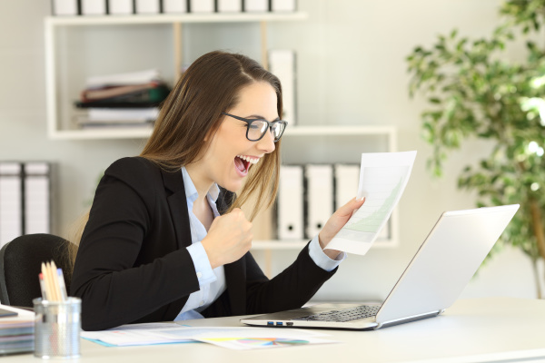 excited office worker checking earnings graph