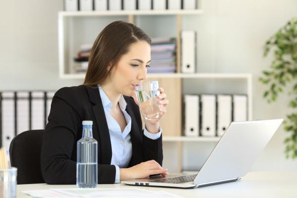 office worker drinking water working on