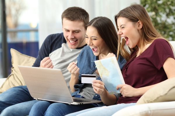 excited friends buying trip on line