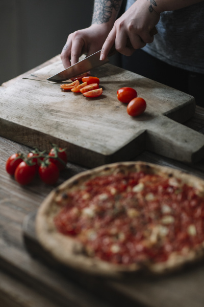 young woman preparing pizza cutting tomatoes