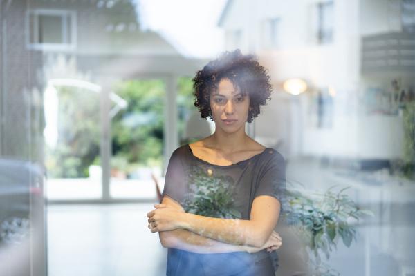 portrait of woman standing behind window