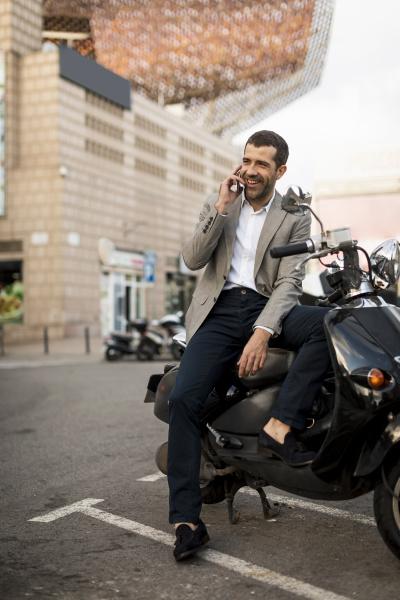 smiling businessman on motorscooter talking on