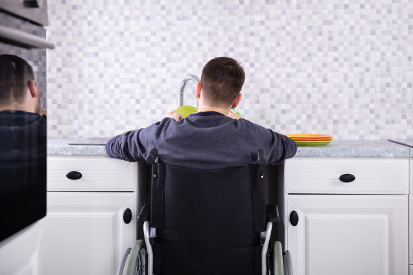handicapped man cleaning dishes in kitchen