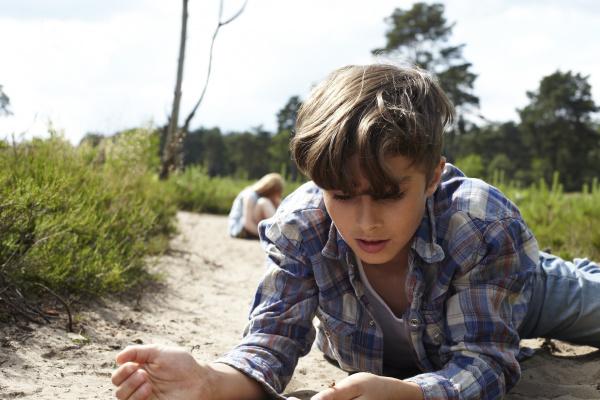 boy lying on sandy path watching