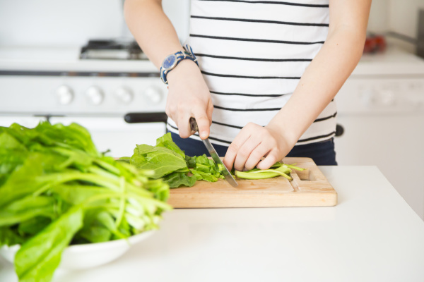girl chopping vegetable in the kitchen