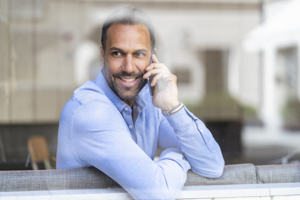 smiling businessman on cell phone behind