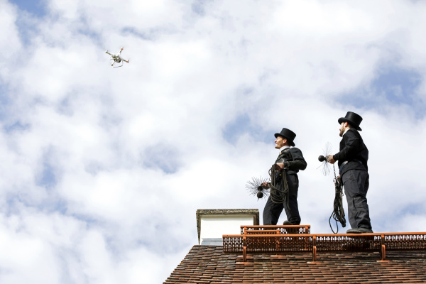 two chimney sweeps on house roof