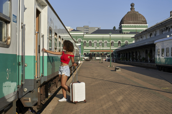 woman with suitcase at train station