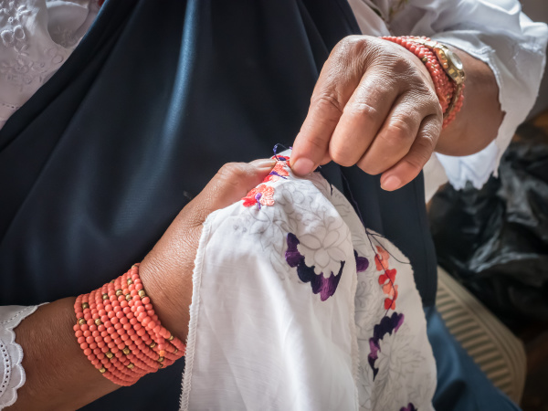indigenous woman doing traditional embroidery