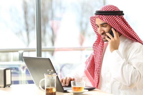 happy arab man using a laptop