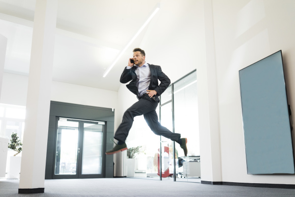 businessman on cell phone jumping in