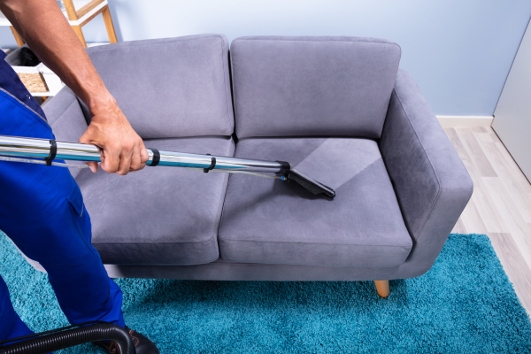 man, cleaning, sofa, with, vacuum, cleaner - 27213887