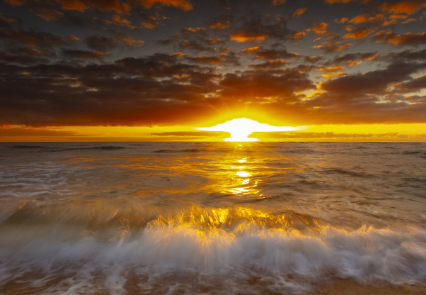 bright golden sunrise over beach and