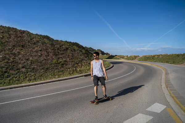 young man longboarding on empty country