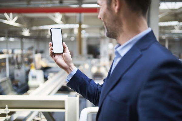 businessman using cell phone in factory