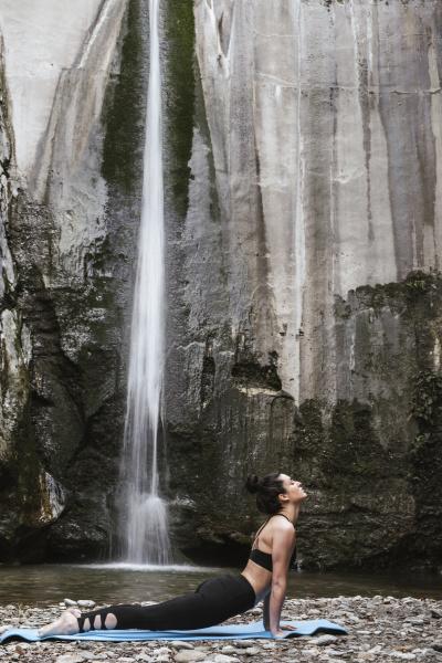 woman practising yoga at waterfall