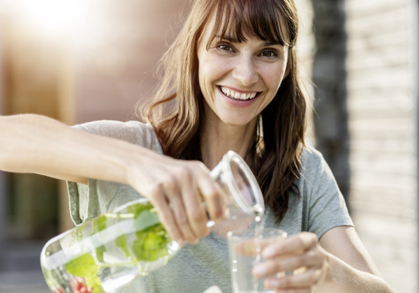 portrait of happy woman pouring infused
