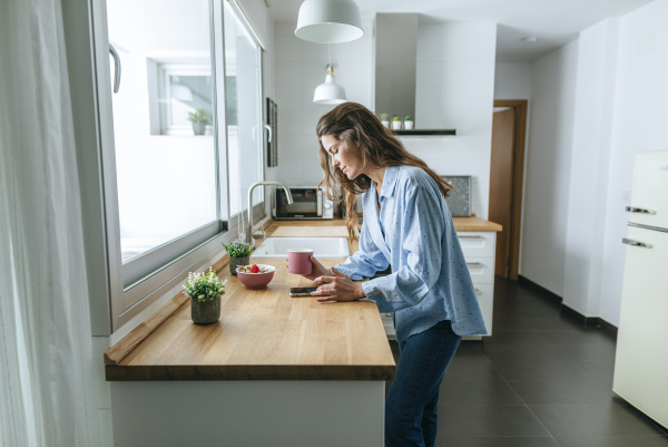 young woman wearing pyjama in kitchen