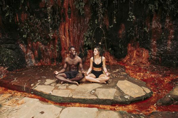 couple meditating at a waterfall