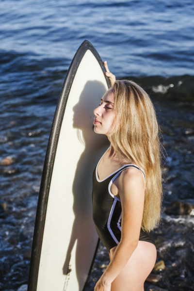 female teenager with surfboard at stony