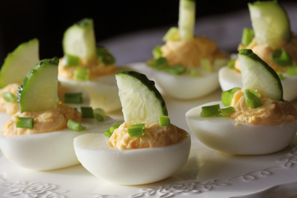 spicy deviled eggs garnished with cucumber