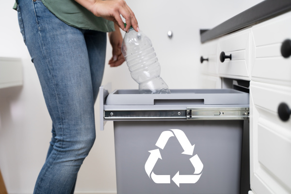 woman throwing plastic bottle in recycling