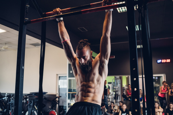 young man training in gym swinging