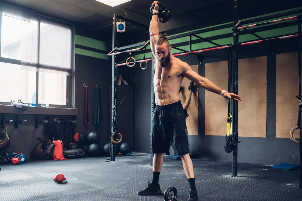 young man training in gym lifting