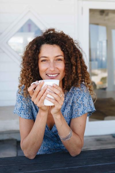 woman enjoying hot drink clasped in