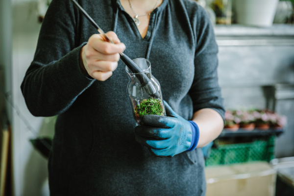 woman filling glass bottle with plants