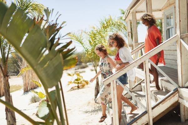 women friends on sunny beach hut