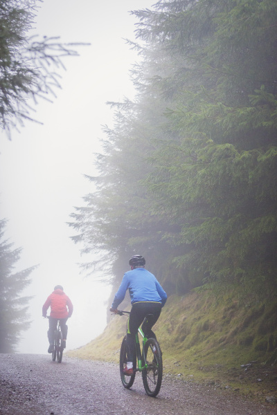 couple mountain biking in rain