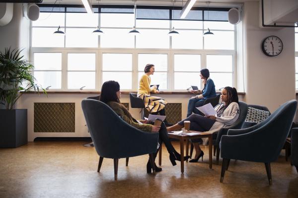 businesswomen talking in open plan office