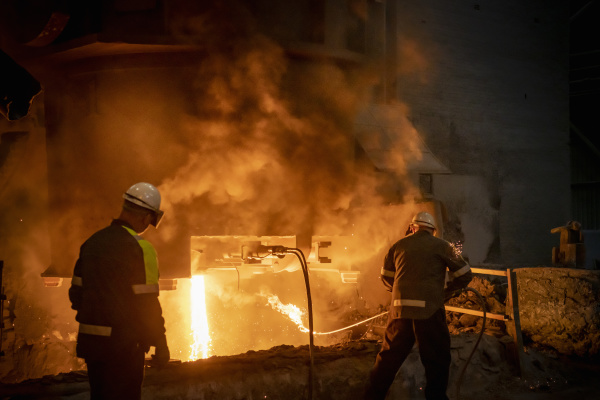 steelworkers testing pour of molten steel