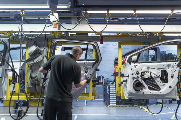 worker on car door assembly line