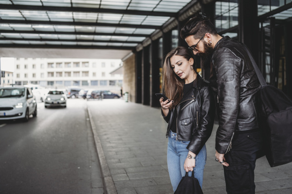 couple using smartphone outside station