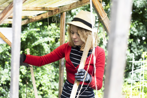 mid adult woman constructing wooden shelter