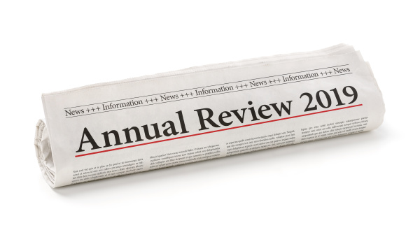 rolled newspaper with the headline annual