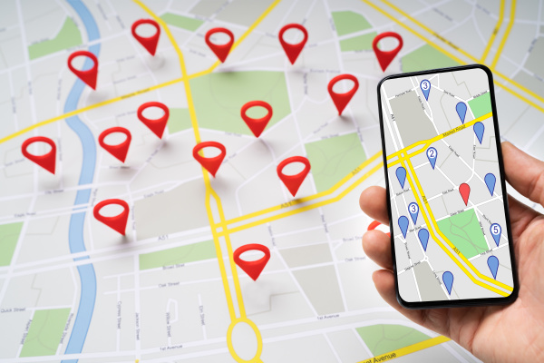person holding mobile phone against map