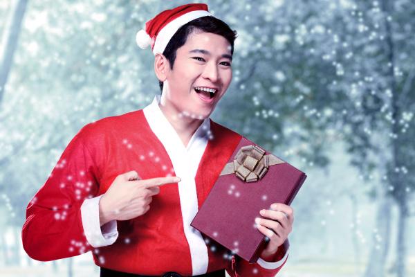 asian man in santa costume holding