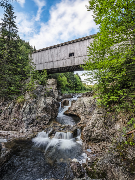 historic covered bridge over creek and