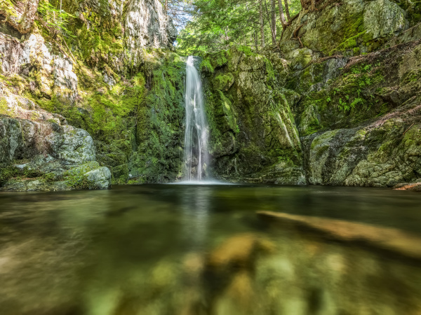 waterfall over green mossy cliff saint