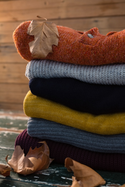 stack of sweater by wall