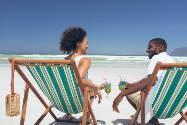 young couple relaxing on sun lounger