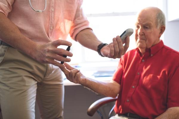 confident male doctor examining senior man