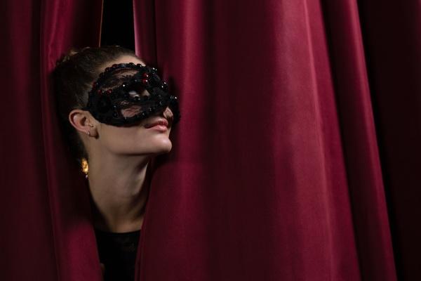 female artist in mask peeking through