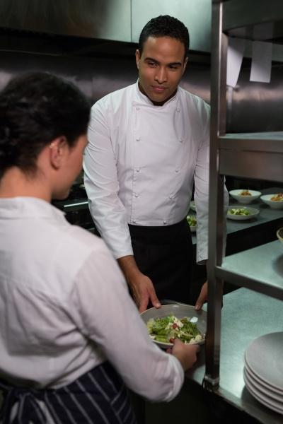 chef handing food dish to waitress