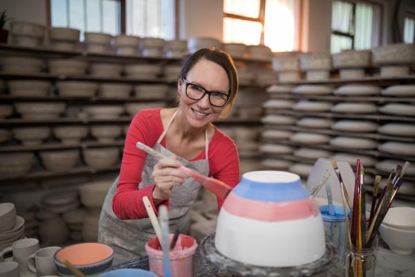 portrait of female potter painting bowl