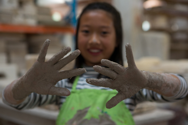 happy girl showing her muddy hand