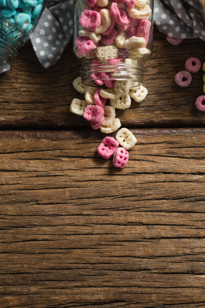 scattered cereals from jar on wooden